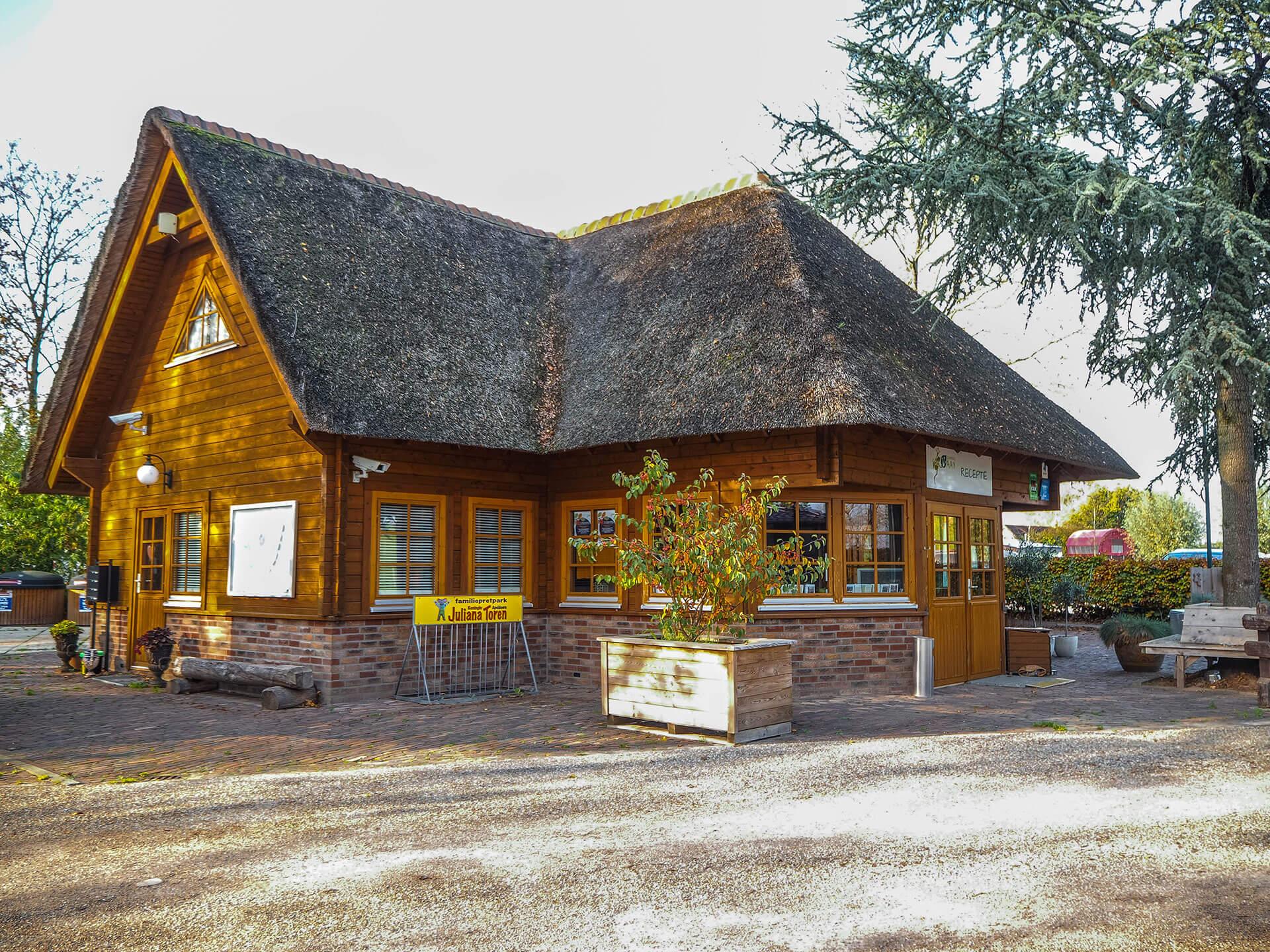Houten receptiegebouw op camping de Waay blokhuis met rieten kap