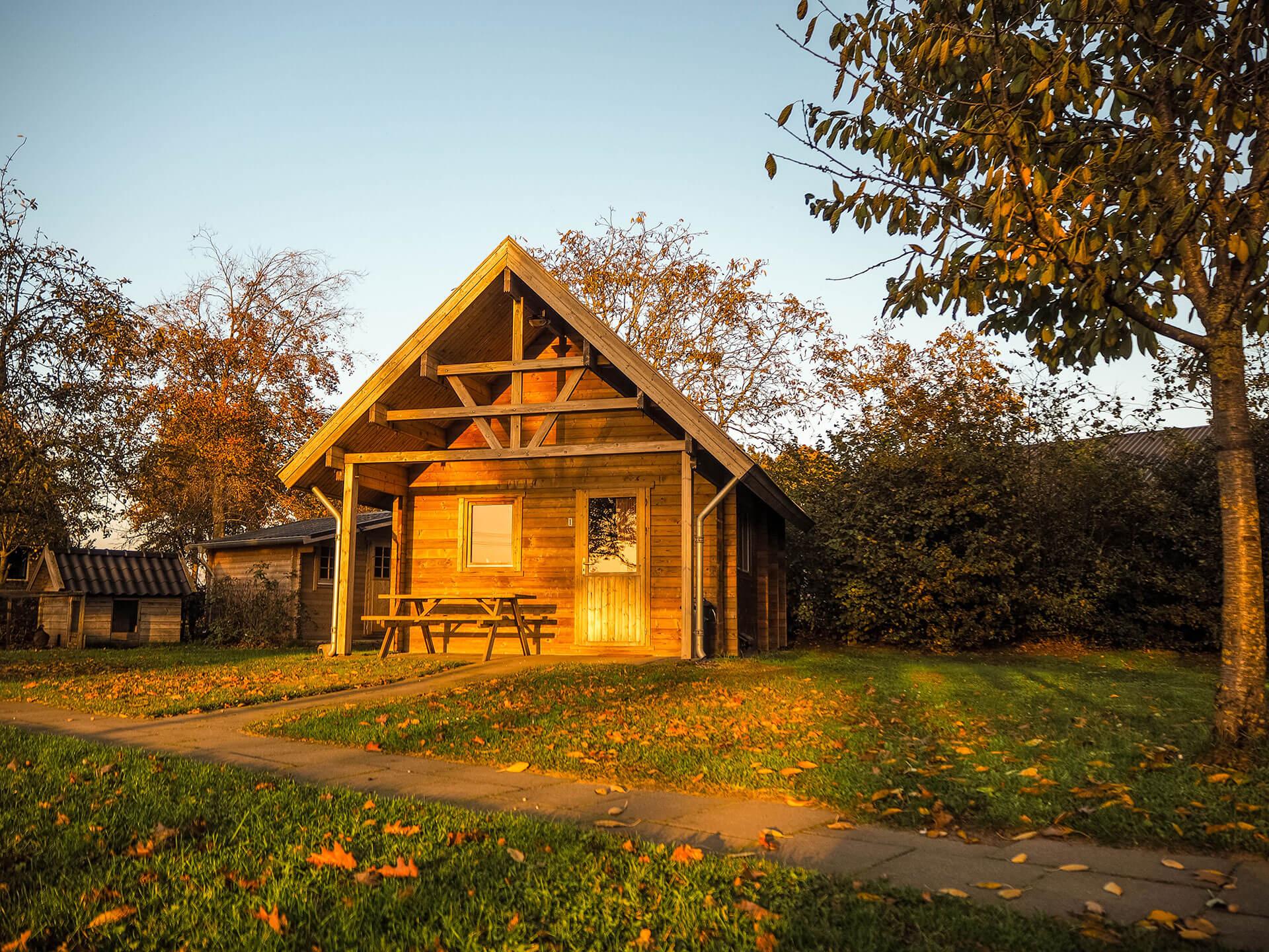 Houten blokhut in de zonsondergang op camping het Wisbroek