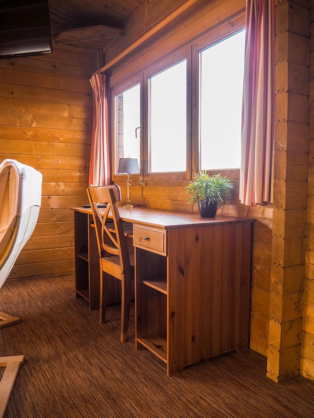 interieur in een houten blokhuis, home office, klein bureau in de woonkamer