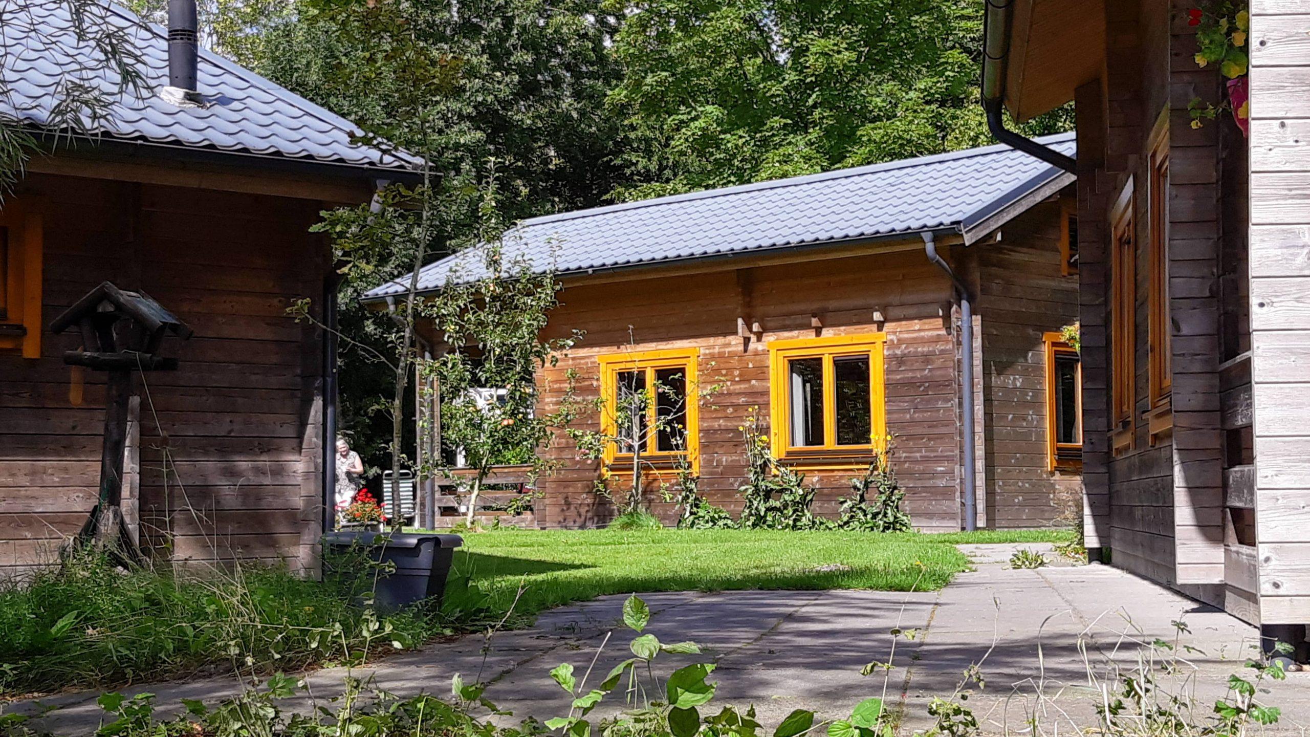 Doorkijk bij houten blokhuizen camping t Ol Gat